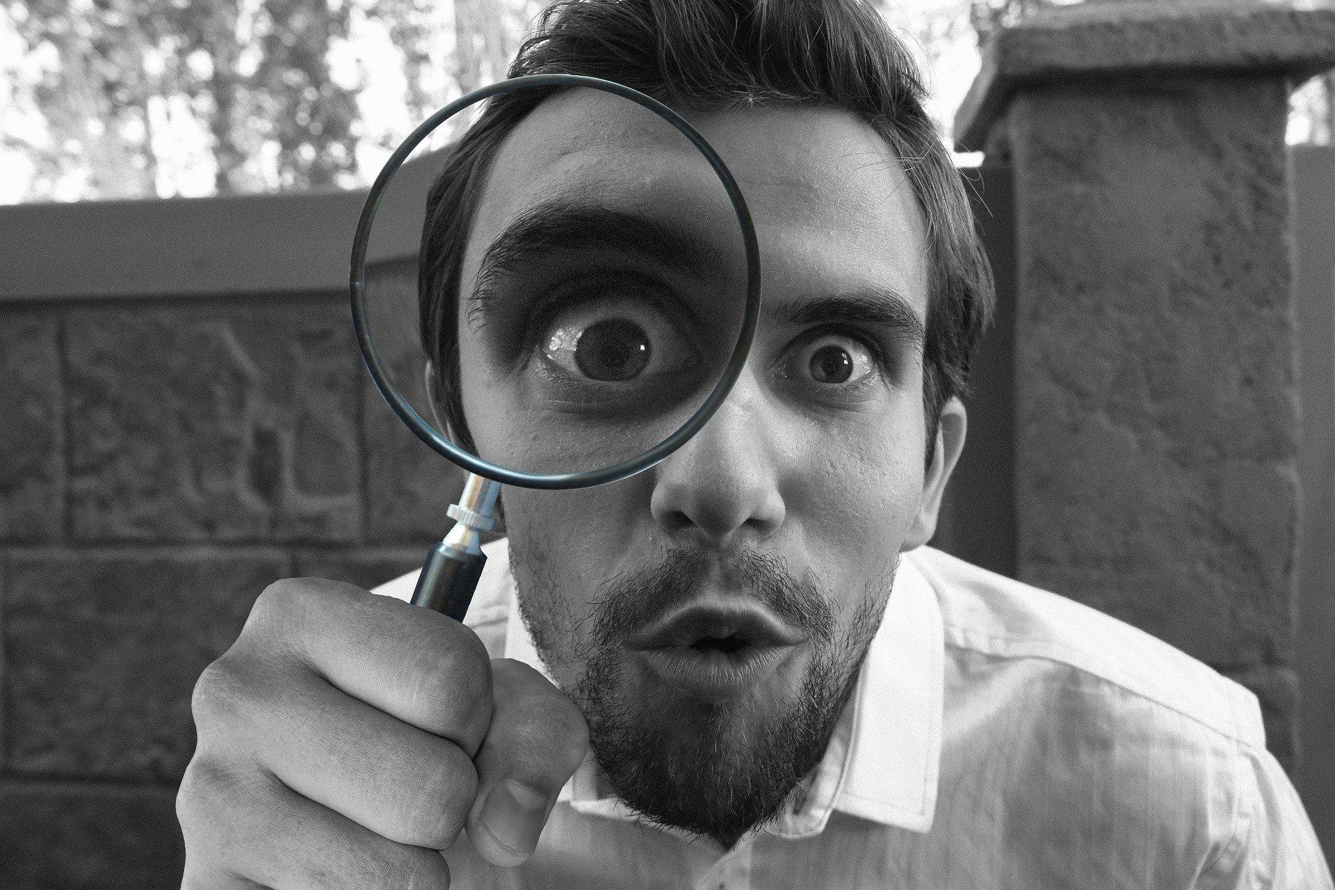 detective che indaga con lente d'ingrandimento